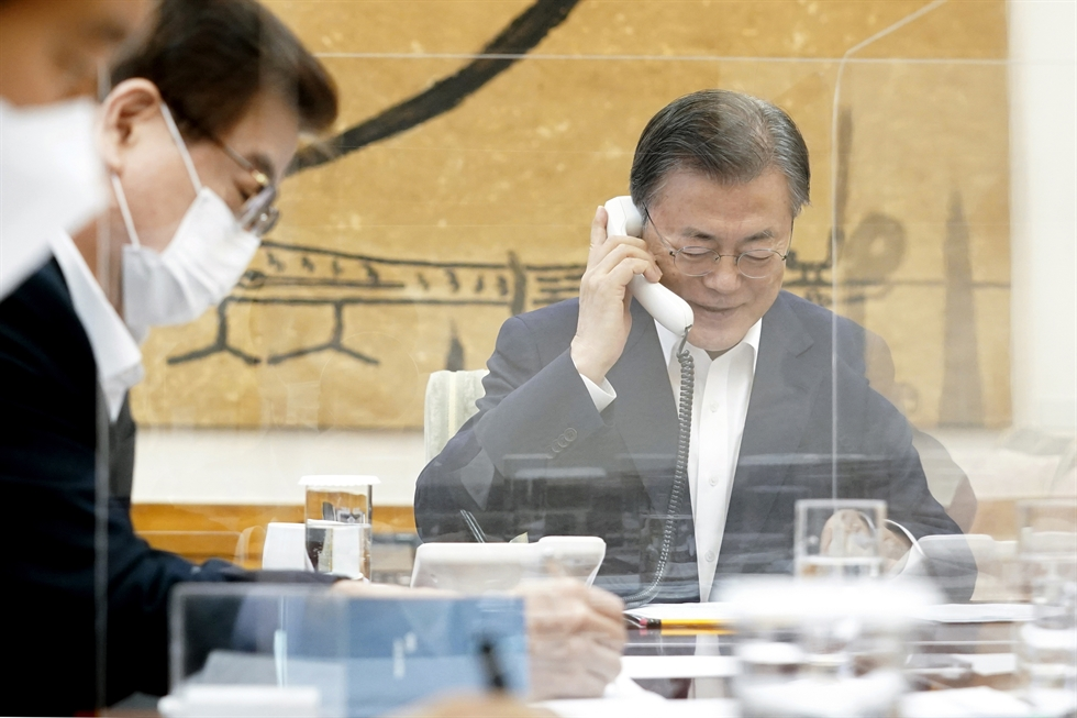 President Moon Jae-in, left, speaks on the phone with U.S. President Joe Biden, Thursday, for the first time since the new U.S. leader took office last month. Yonhap