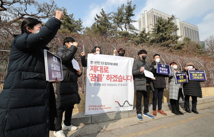 Members of an association of cafes, restaurants and bars in South Korea demand restitution from the central government for their business losses in front of the Seoul Central District Court in Seocho District, Feb. 19. The protesters claimed their businesses were seriously affected after the government enforced them to end their business hours earlier than usual to minimize the spread of COVID-19. Yonhap