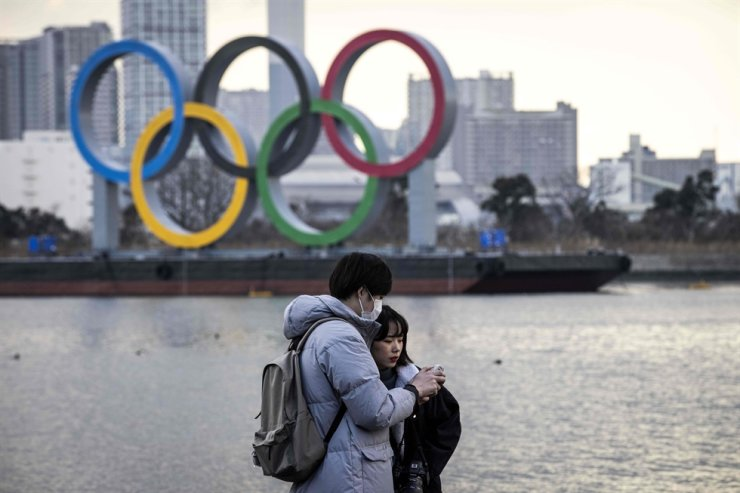 A couple check pictures after posing in front of the Olympic rings on display at the Odaiba waterfront in Tokyo on Feb. 2, 2021. AFP
