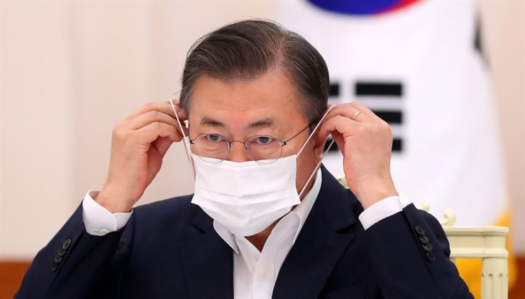 President Moon Jae-in puts on a face mask during a meeting with senior members of the ruling Democratic Party of Korea at Cheong Wa Dae, Friday. Yonhap