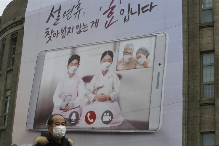 A man wearing a face mask as a precaution against the coronavirus passes by a banner calling on residents to refrain from visiting families and relatives during the upcoming Lunar New Year holidays that start Feb. 11, in front of Seoul City Hall in Seoul, Monday, Feb. 1, 2021. AP