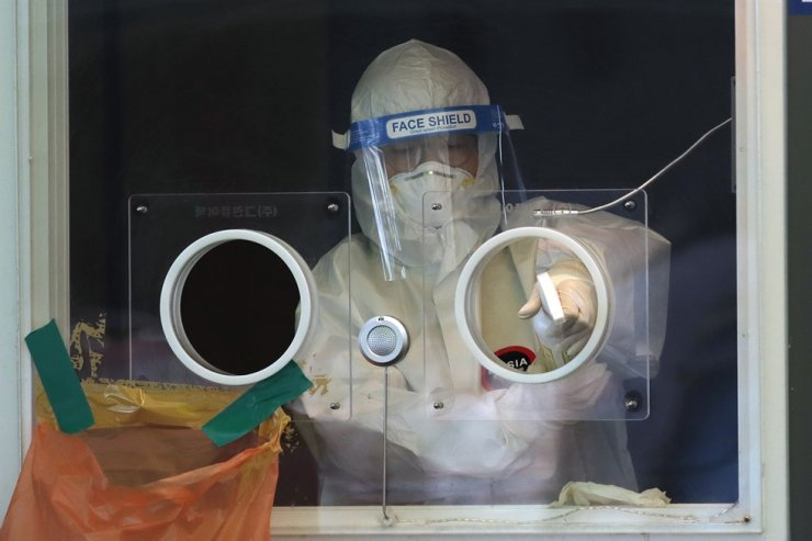 A medical worker wearing protective gear sprays disinfectant in the sub-zero temperatures at a coronavirus testing site in Seoul, Thursday, Feb. 18, 2021. AP