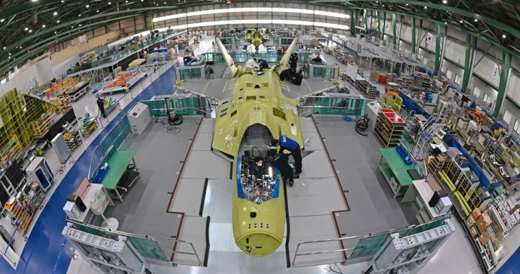 Workers of Korea Aerospace Industries (KAI) assemble the first prototype of the nation's indigenous fighter jet program KF-X at a plant in Sacheon, South Gyeongsang Province, Jan. 22. / Korea Times file