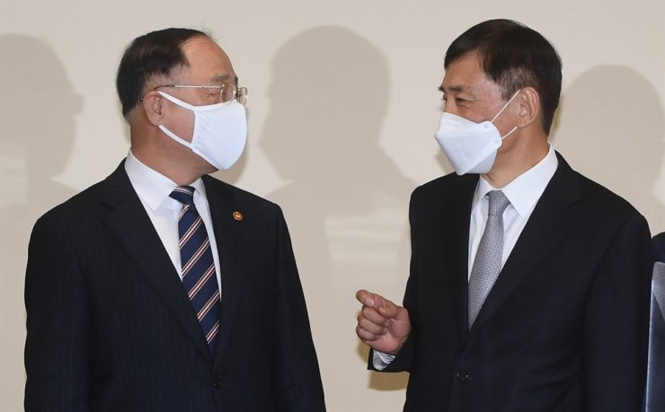 Finance Minister Hong Nam-ki, left, talks with Bank of Korea Governor Lee Ju-yeol at the Korea Federation of Banks headquarters in Seoul, Thursday, before the beginning of a macroeconomic meeting. Yonhap