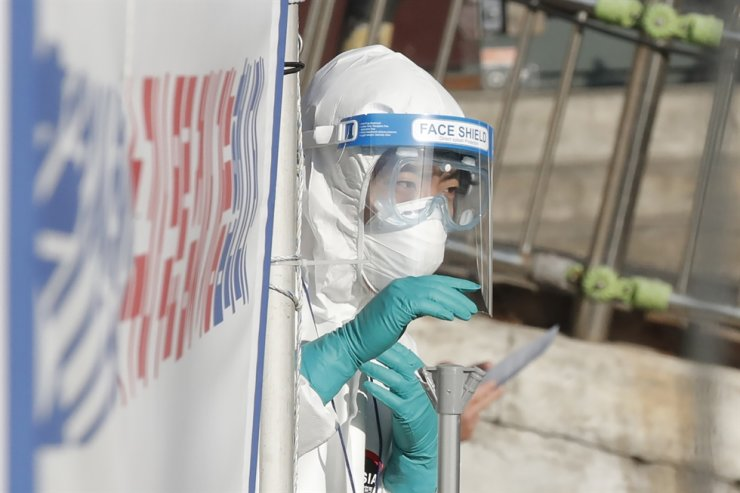 A medical worker wearing protective gear gestures at a coronavirus testing site in Seoul, Tuesday, Feb. 9, 2021. AP
