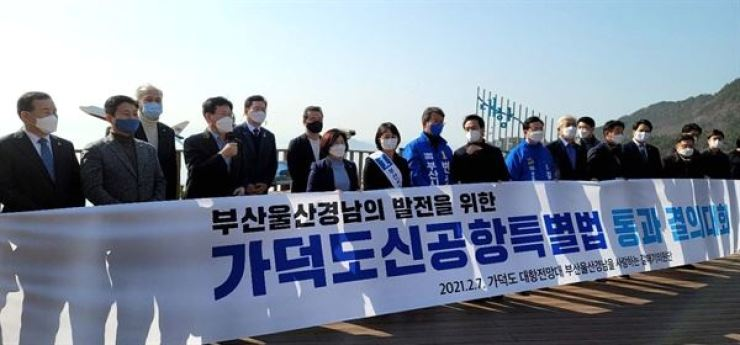 Members of the ruling Democratic Party of Korea hold a rally urging the National Assembly to pass a special bill for the construction of an airport on Gadeok Island in Busan, Feb. 7. Korea Times file
