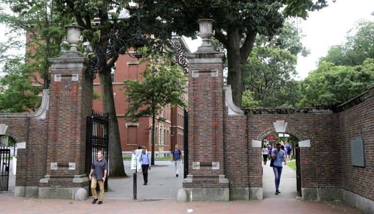 In this Aug. 13, 2019, file photo, pedestrians walk through the gates of Harvard Yard at Harvard University in Cambridge, Mass. AP-Yonhap