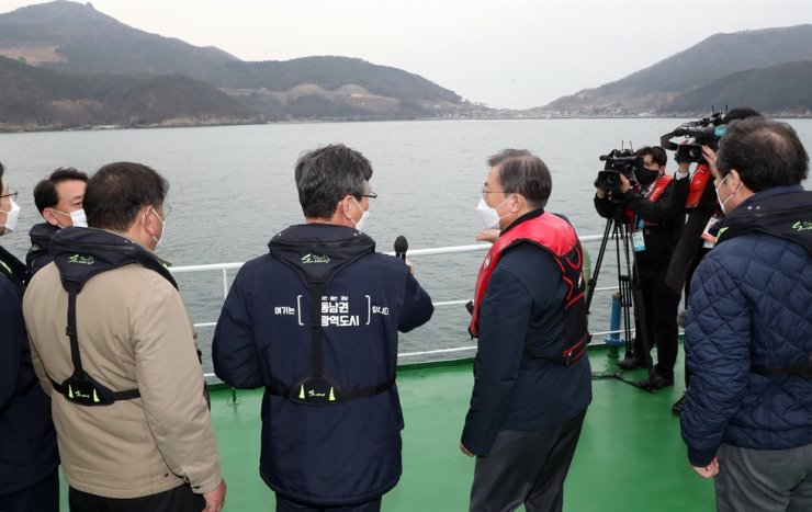 President Moon Jae-in listens to a report from Acting Busan Mayor Lee Byung-Jin about a plan to build a new international airport on Busan's Gadeok Island, during his inspection of the site, Thursday. Yonhap
