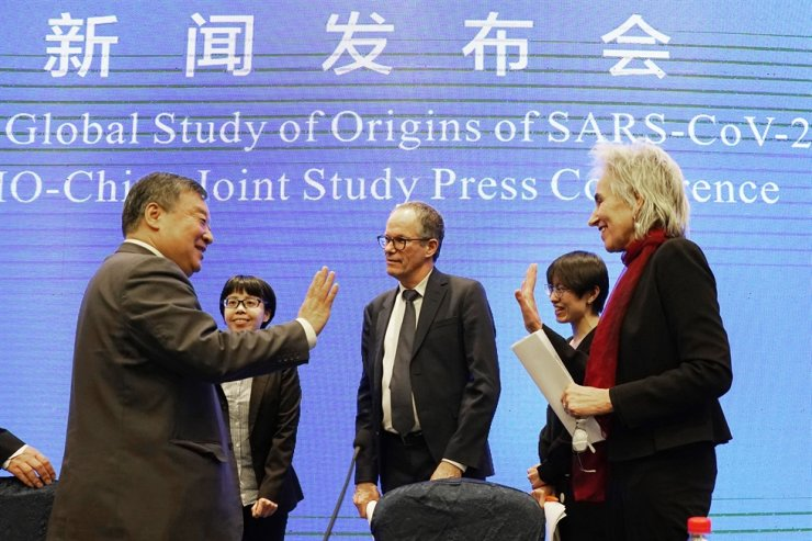 Marion Koopmans, right, and Peter Ben Embarek, center, of the World Health Organization team say farewell to their Chinese counterpart Liang Wannian, left, after a WHO-China Joint Study Press Conference held at the end of the WHO mission in Wuhan, China, Tuesday, Feb. 9, 2021. AP