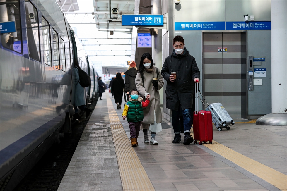 A family of three walk down the stairs at Seoul Station, Wednesday, to catch a train bound for Daegu, where the little boy's grandmother lives, for the Lunar New Year holiday. To contain the spread of COVID-19, the government has put in place special measures for the holiday, including selling only window seats on trains and charging toll fees on highways. A ban on gatherings of five or more people also remains effective. Korea Times photo by Shim Hyun-chul