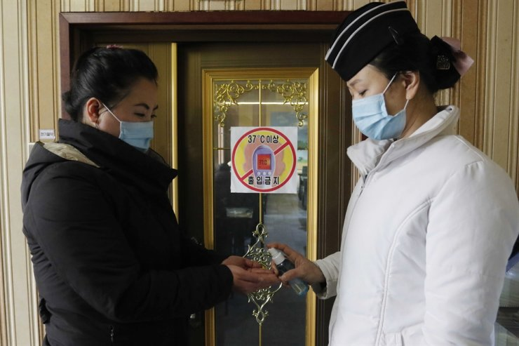 A staff member of the Pongnam Noodle House, right, disinfects the hands of a woman coming into its restaurant in Pyongyang, Feb. 5. AP-Yonhap