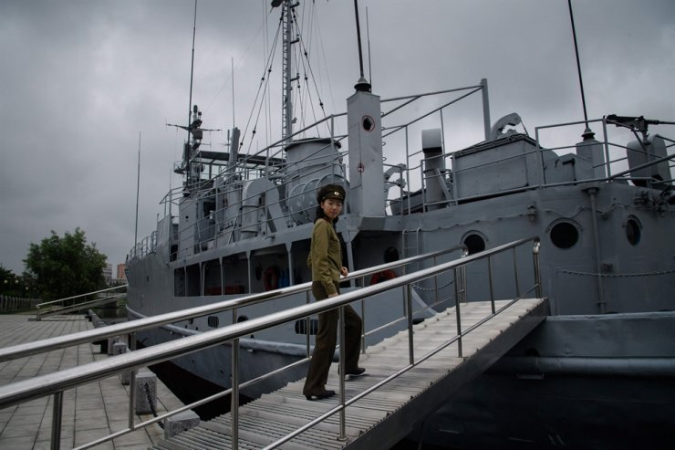 In a photo taken on July 28, 2017, a Korean People's Army guide walks aboard the USS Pueblo at the Victorious Fatherland Liberation War Museum in Pyongyang, North Korea. A U.S. court has ordered North Korea to pay damages to the crew and family of the spy ship USS Pueblo, who were tortured and mistreated for 11 months in 1968 after being captured by the North Korean navy. AFP