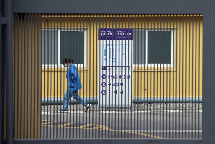A medical worker passes by a state-run COVID-19 vaccination center run by the National Medical Center in central Seoul, Sunday. Yonhap