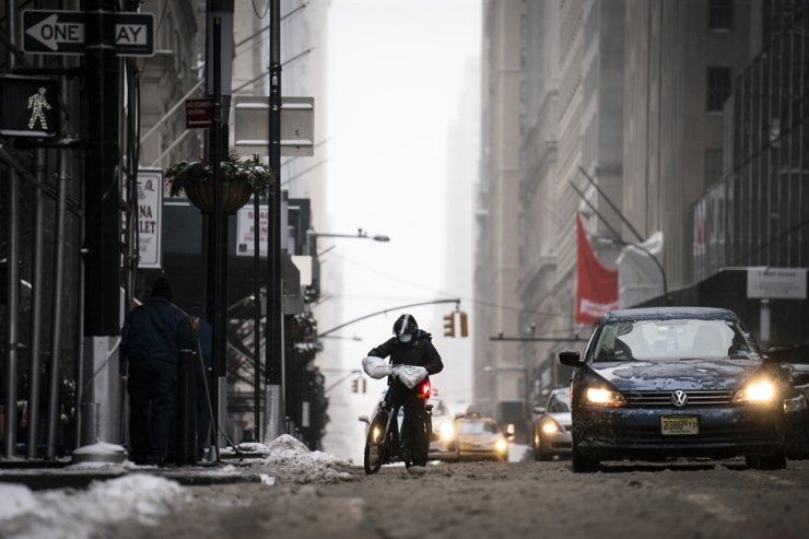 A bicycle delivery worker passes down Broadway struggles through slush under snowfall in the Financial District in the Manhattan borough of New York, Thursday, Feb. 18, 2021. AP