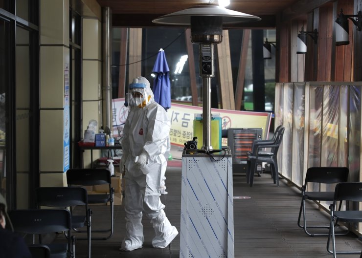 A medical worker wearing a protective suit sprays disinfectant as a precaution against the coronavirus at a coronavirus testing site in Seoul, Thursday, Feb. 25, 2021. AP