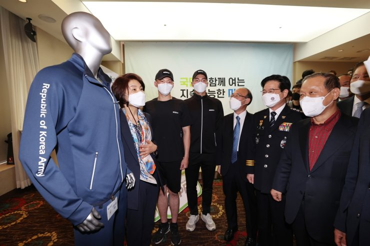 Environment Minister Han Jeoung-ae, second from left, poses next to clothes made from recycled plastic bottles, which will be the new sportswear for members of the Army, at the Hotel President in Seoul, March 15. Yonhap