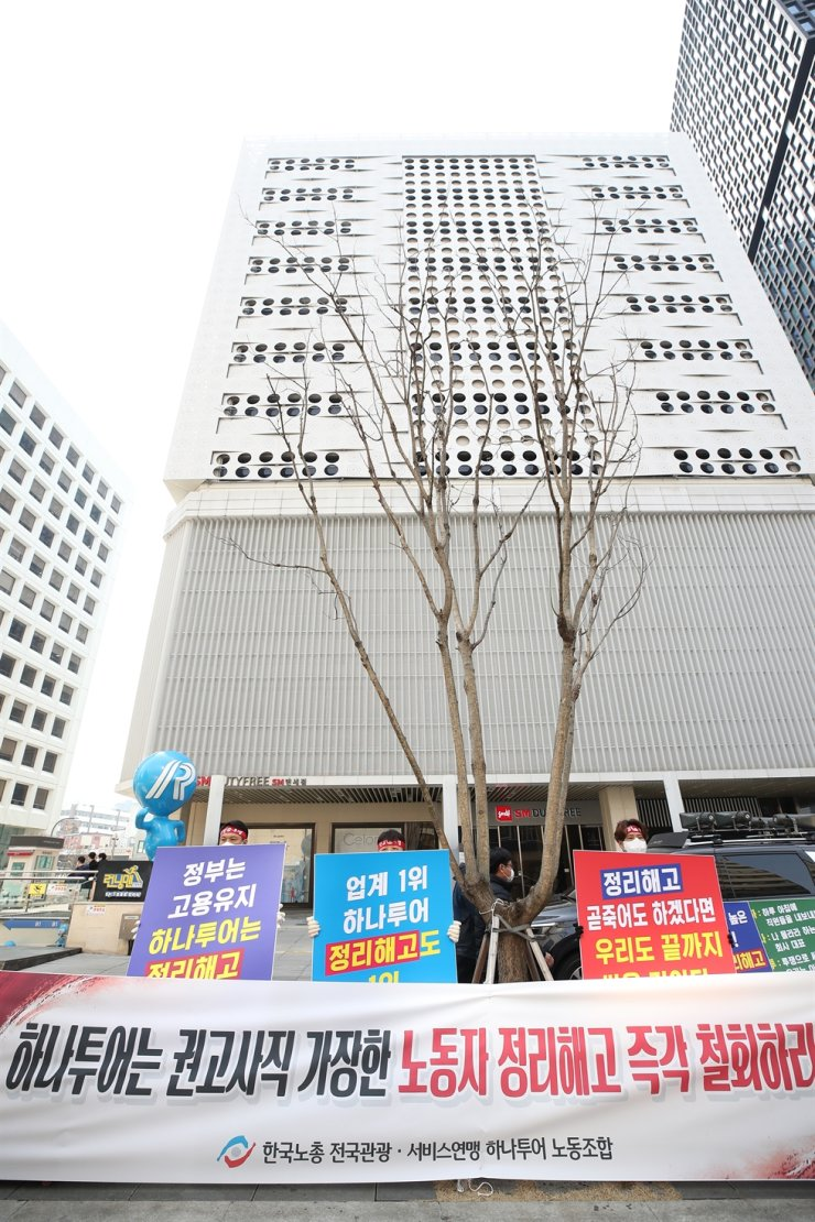 Hanatour Service union members hold a rally in front of the tour agency's headquarters building in Seoul, March 3, calling for the company to withdraw its plan for layoffs. Yonhap