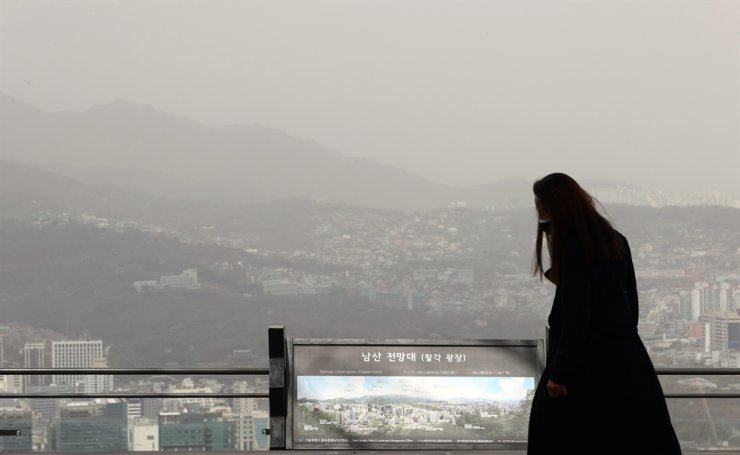 A woman walks on a trail on Mount Nam, Seoul, Monday, while the sky is covered with yellow dust. Korea had 'very bad' levels of fine dust and ultrafine dust, with dust alerts being issued across the country, after a yellow dust storm originating from inland deserts in northern China blanketed the nation. Yonhap