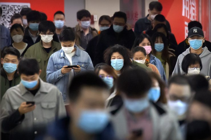 In this April 9, 2020, file photo, commuters wearing face masks walk through a subway station in Beijing. Speculation is running rampant about how many years of pension income may be lost after the Chinese government announced plans to gradually increase the nation's mandatory retirement age. AP