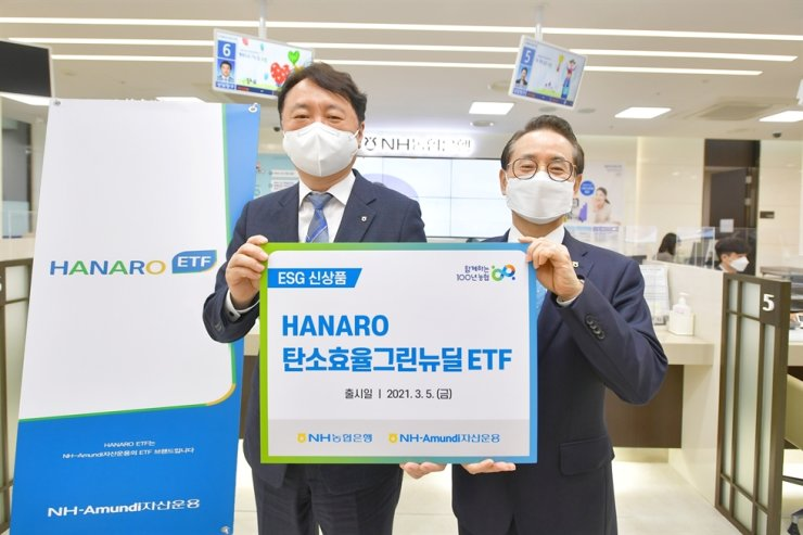 NongHyup Bank CEO Kwon Jun-hak, left, poses with NH-Amundi Asset Management CEO Park Hak-joo after registering to the latter's HANARO Carbon Efficient Green New Deal exchange traded fund (ETF), Friday. The ETF invests in companies planning to reduce their carbon emissions and pursue environmental, social and corporate governance values. Courtesy of NongHyup Bank