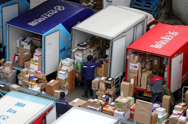 Delivery workers load parcels onto trucks at a logistics hub in Seoul in this March 17, 2020 photo. Yonhap