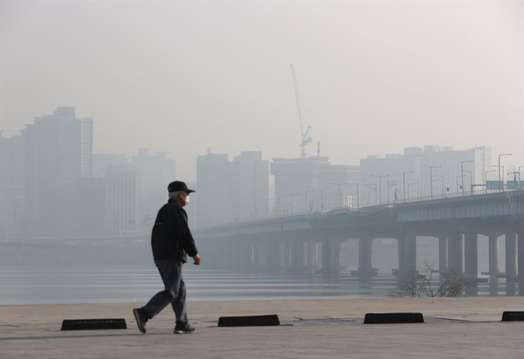 A man walks along the Han River near Yeouido in Seoul, Thursday, when instances of ultrafine dust concentration reached 'bad' and 'very bad' levels across the country. The interior of the nation is also likely to have high levels of fine dust Friday. Yonhap