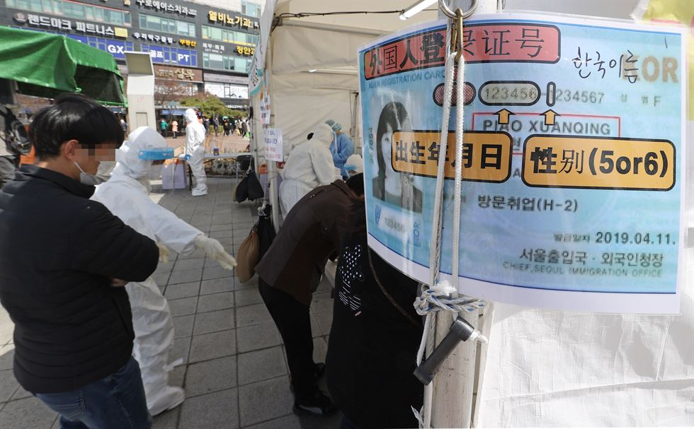 Foreign workers line up to take coronavirus tests in Ansan, Gyeonggi Province, Tuesday, as local authorities ordered all foreign workers there to undergo testing by March 22. Yonhap