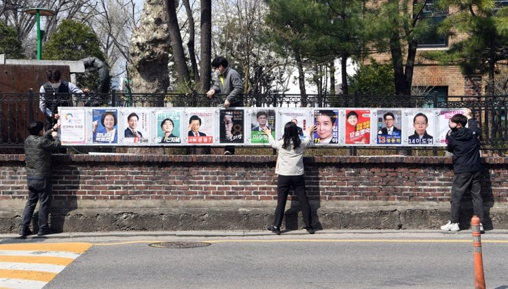 Staffers from the Seoul branch of the National Election Commission put posters of Seoul mayoral by-election candidates on a fence in Jongno District, central Seoul, March 25. Twelve candidates are running for the race slated for April 7. Yonhap