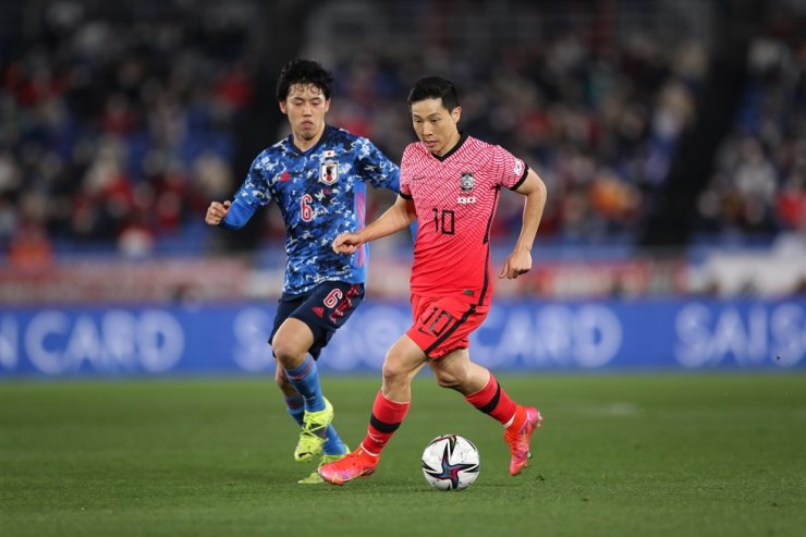 Nam Tae-hee of South Korea, right, tries to dribble past Wataru Endo of Japan during their friendly football match at Nissan Stadium in Yokohama, Japan, March 25. Yonhap