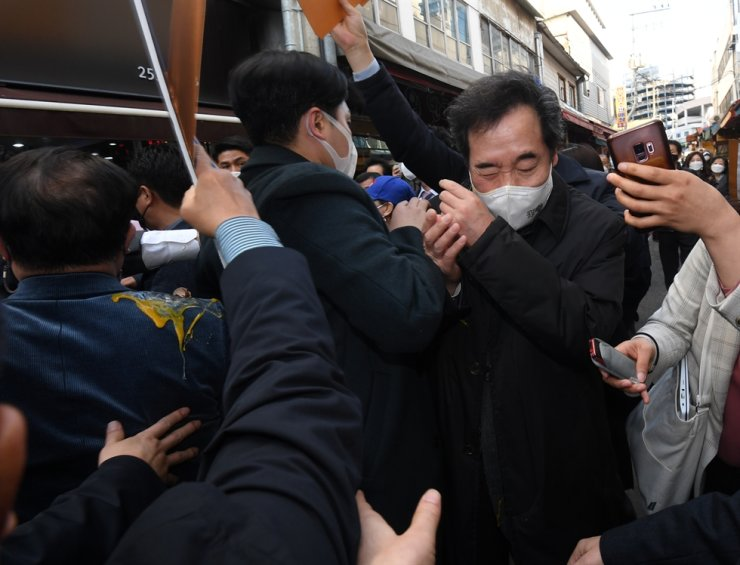 Ruling Democratic Party of Korea Chairman Lee Nak-yon flinches after getting hit by an egg in his face while visiting a marketplace in Chuncheon, Gangwon Province, March 5. Yonhap