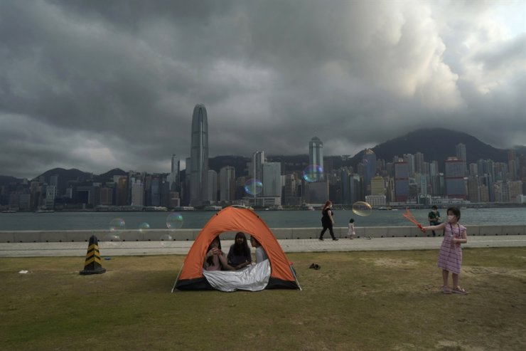 People wearing face masks spend time at a park in the West Kowloon Cultural District of Hong Kong, March 29. Hong Kong's travel industry has called on government officials and its prospective travel bubble partners to strike bilateral agreements recognizing each other's approved COVID-19 vaccines in order to get the long-awaited deals off the ground. AP