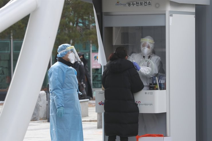 A medical worker takes samples from a woman for a COVID-19 test at a makeshift clinic in Dongducheon, Gyeonggi Province, Tuesday. Yonhap