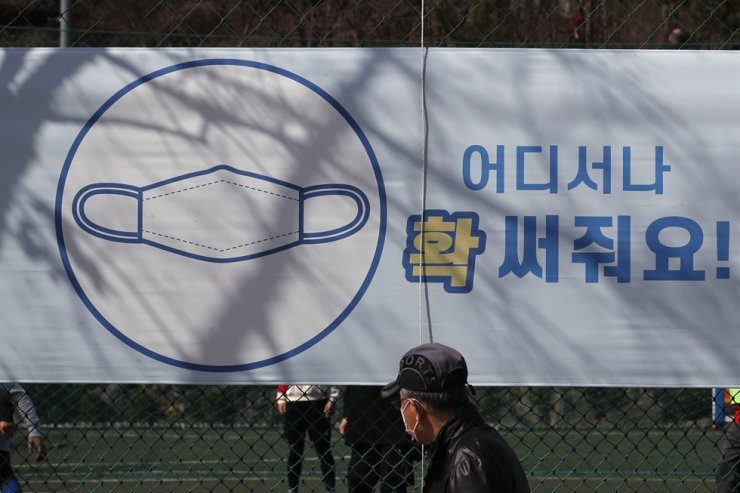 A man wearing a mask as a precaution against the coronavirus walks near a banner at a park in Seoul, Friday, March 5, 2021. AP
