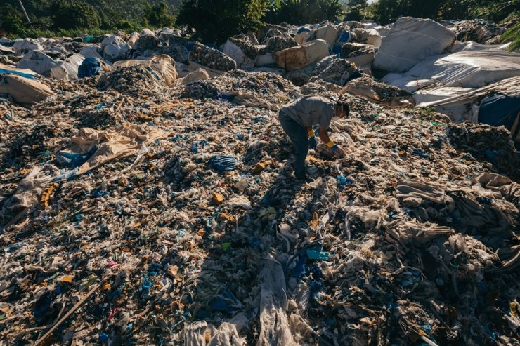 An employee of Greenpeace Southeast Asia's Filipino Office on Dec. 6, 2018, inspects some 5,100 tons of waste on Misamis Oriental in the Philippine's Mindanao Island, which were illegally exported from Korea earlier that year. Courtesy of Greenpeace
