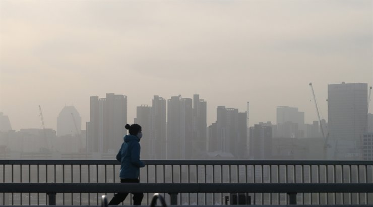 A woman wearing a face mask crosses a bridge in southern Seoul, Tuesday. A strong yellow dust storm originating from China and Mongolia continued to blanket Korea for the second day. Yonhap
