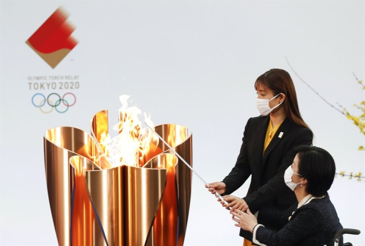 Japanese Actor Satomi Hishihara, back, and Paralympian Aki Taguchi light the celebration cauldron on the first day of the Tokyo 2020 Olympic torch relay in Naraha, Fukushima prefecture, Japan, March 25. EPA