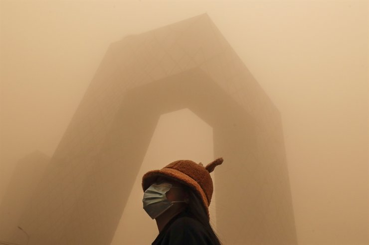 A woman wearing a face mask to help curb the spread of the coronavirus stands against the China Central Television building as capital city is hit by polluted air and a sandstorm in Beijing, Monday, March 15, 2021. AP