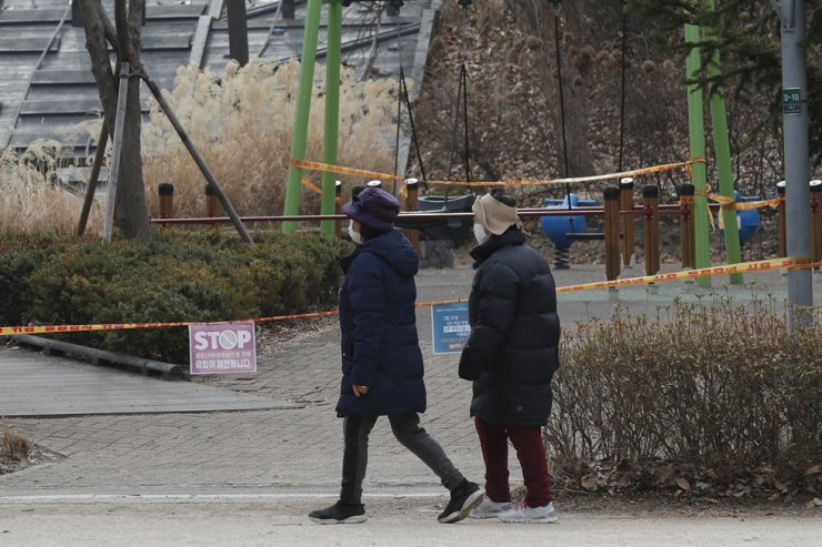 Visitors wearing face masks as a precaution against COVID-19 walk past a section of a public park in Seoul taped off with a sign that reads 'Access restricted to prevent the spread of COVID-19,' March 4. AP