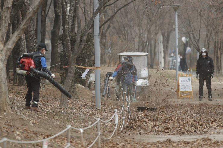 Workers wearing face masks as a precaution against the coronavirus gather fallen leaves at a park in Seoul, Thursday, March 4, 2021. AP