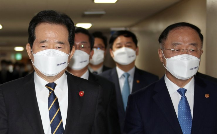 Finance Minister Hong Nam-ki, right, and Prime Minister Chung Sye-kyun enter a briefing room to announce the government's anti-real estate speculation measures at Government Complex Seoul, Monday. Yonhap