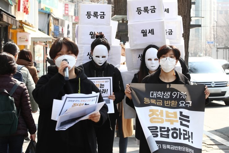 Protesters march from Gyeongbok Palace Station in Seoul's Jongno District toward Cheong Wa Dae on Mar. 8 demanding the South Korean government restitute tuition fees for university students or propose alternative measures for those who couldn't normally attend their post-secondary schools and pay rents for their homes due to COVID-19 risks. Yonhap