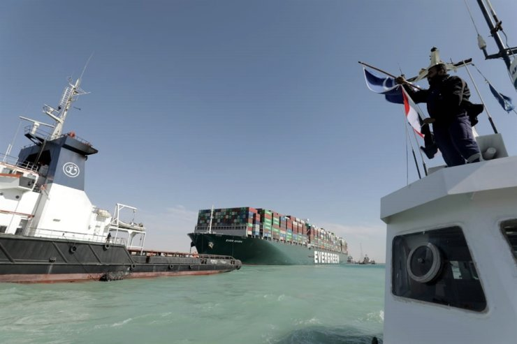 A handout photograph made available by the Suez Canal Authority shows tugboats near the Ever Given container ship after it was refloated in the Suez Canal, Egypt, March 29. The head of the Suez Canal Authority announced that the large container ship, which ran aground in the Suez Canal, is now free floating after responding to the pulling maneuvers. EPA