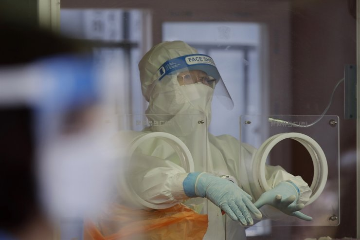 A medical worker wearing protective gear prepares to take a sample at a temporary screening clinic for coronavirus in Seoul, April 10. AP