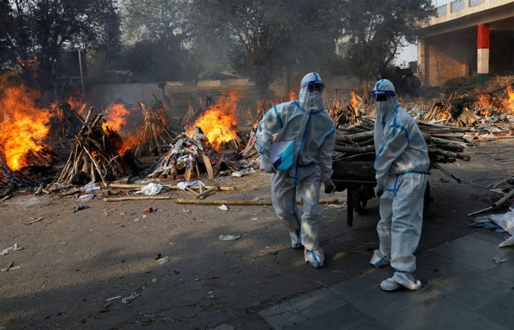 Health workers wearing personal protective equipment carry wood to prepare a funeral pyre for a coronavirus disease victim during a mass cremation at a crematorium in New Delhi, India, April 26. Korea's foreign ministry said Tuesday that it would help Korean citizens in India return to Korea safely. Reuters-Yonhap