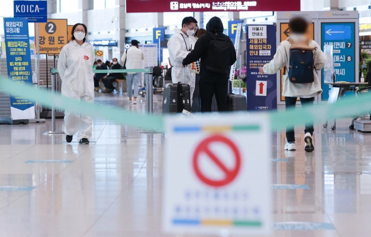 Arriving passengers are guided by a quarantine official at Incheon International Airport, Tuesday. Yonhap