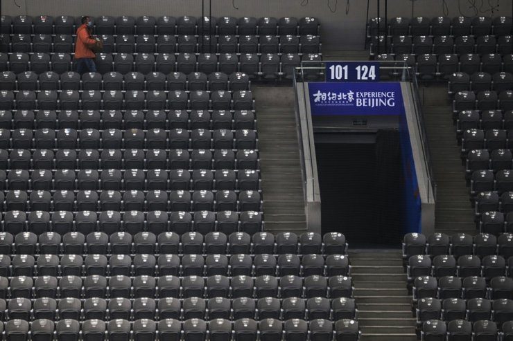 A worker wearing a face mask walks by seats at the ice hockey venue for the 2022 Beijing Winter Olympics during a test event at the National Indoor Stadium in Beijing, April 1. The Chinese government warned Washington on Wednesday not to boycott the event after U.S. President Joe Biden said he was talking with allies about a joint approach to complaints of human rights abuses. AP