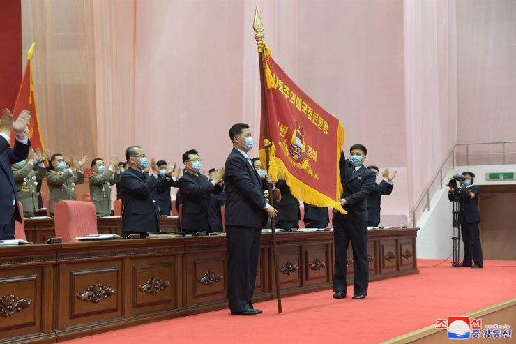 Members of the Kimilsungist-Kimjongilist Youth League clap as a flag bearing the group's new name, 'the Socialist Patriotic Youth League,' is introduced during the group's 10th congress in Pyongyang, according to the Korean Central News Agency on Friday. Yonhap