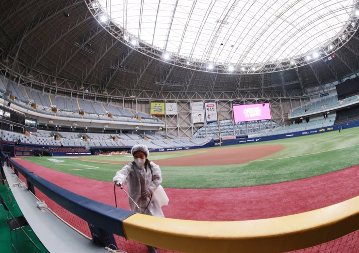 A health worker disinfects inside Gocheok Sky Dome in Seoul's Mapo District, April 2, ahead of the season opening game of Korean Baseball League between the Samsung Lions and Kiwoom Heroes, April 3. Yonhap