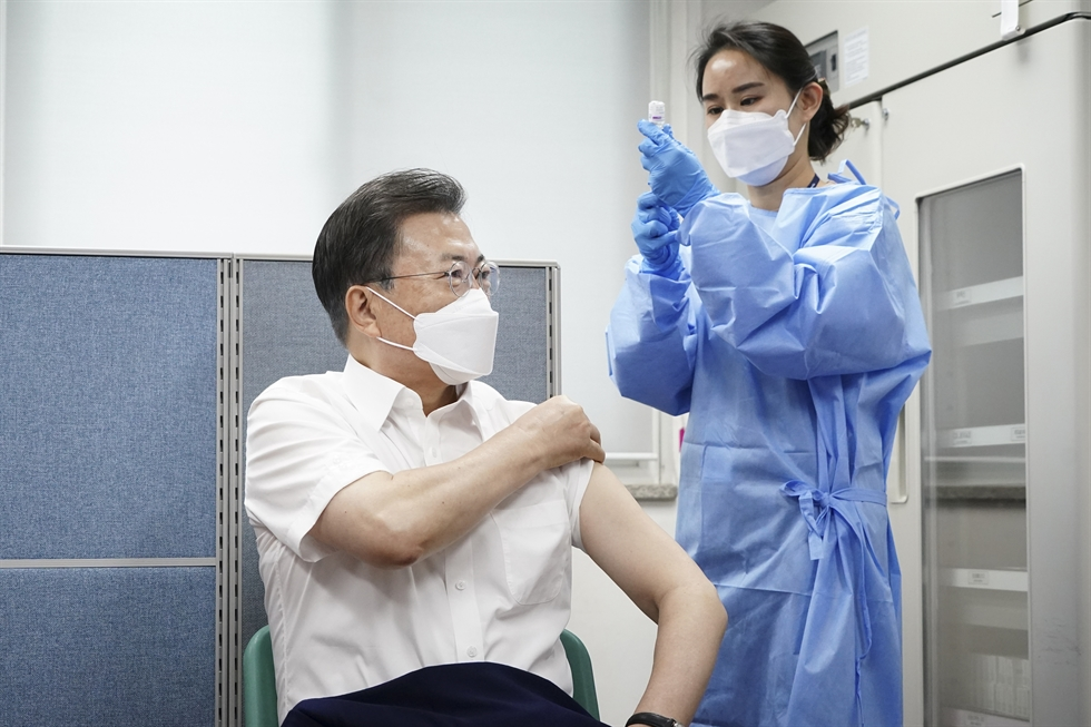 President Moon Jae-in takes off his face mask during a meeting with aides at Cheong Wa Dae, March 22. Yonhap