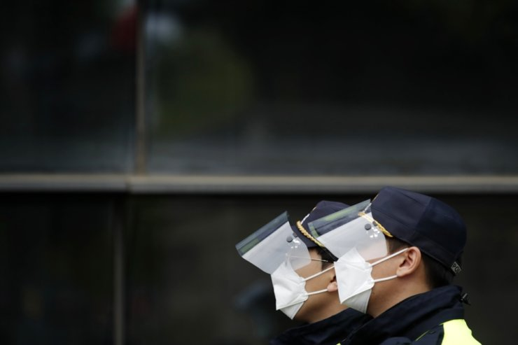 Police officers, wearing face masks as a precaution against the coronavirus, stand near the Japanese Embassy in Seoul, April 27. AP-Yonhap